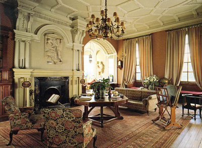 "The library-another lovely room, originally 16th century, but redesigned in Regency style during the early 19th century, with an elegant ivory ""Jacobethan"" ceiling. Above the firepace is a Greek sculpture (350 B.C.) of an Athenian couple."